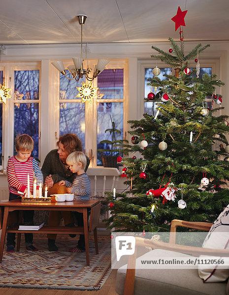 Schweden  Frau und Jungen bei Tisch am Weihnachtsbaum
