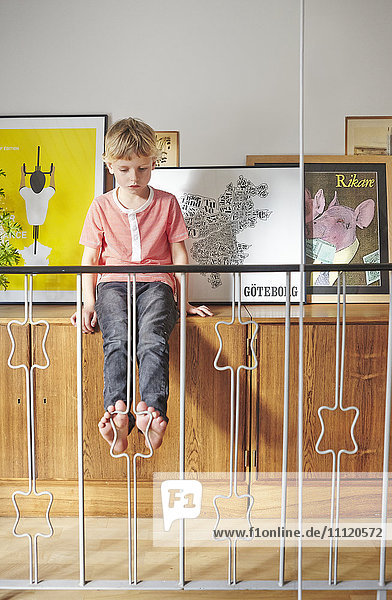 Schweden  Junge sitzend auf Schrank mit Bildern hinter dem Geländer