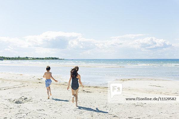 Schweden  Oland  Kopingsvik  Girl (10-11) und Junge (8-9) laufen am Strand