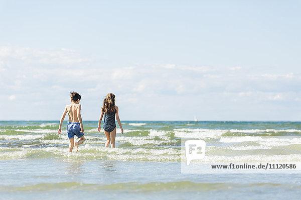 Schweden  Oland  Kopingsvik  Mädchen (10-11) und Junge (8-9)  die ins Meer gehen.