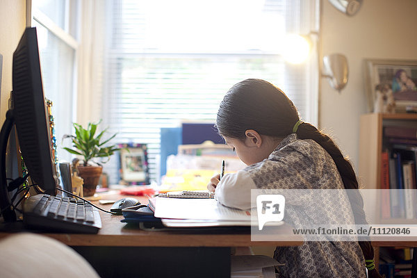 Mixed race girl doing homework at desk