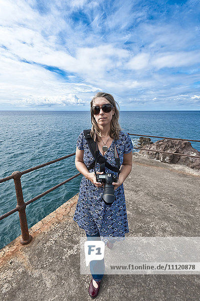 Caucasian woman on jetty with camera