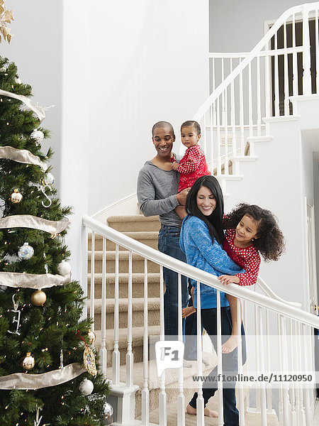 Family descending stairs on Christmas morning