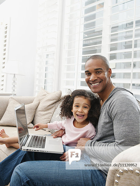 Father and daughter using laptop on sofa