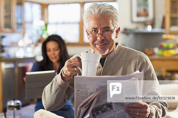 Hispanic man drinking coffee and reading newspaper