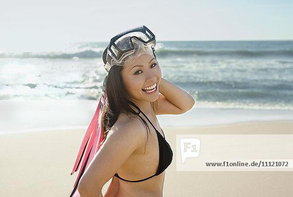 Asian woman wearing goggles at beach