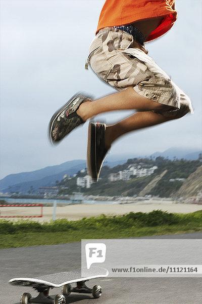 Mixed Race boy jumping over skateboard