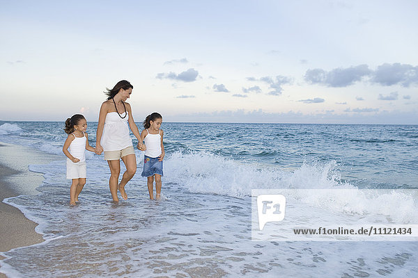 Multi-ethnic mother and daughters walking through ocean surf