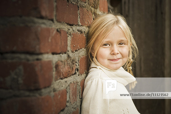 Smiling Caucasian girl leaning on wall Smiling Caucasian girl leaning on wall