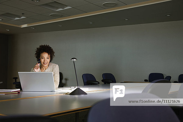 African businesswoman working on laptop in conference room