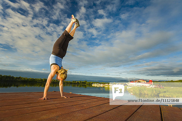Caucasian woman practicing yoga on dock on still lake  Anchorage  Alaska  United States