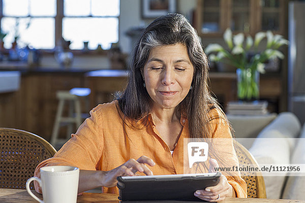 Older Hispanic woman using tablet computer at table