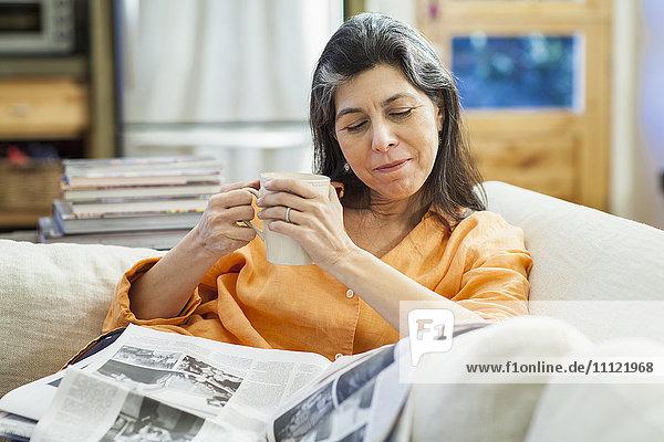 Older Hispanic woman reading newspaper on sofa