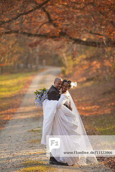 Bride and groom hugging on path