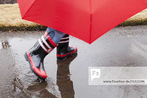 Mixed race boy splashing in rainboots