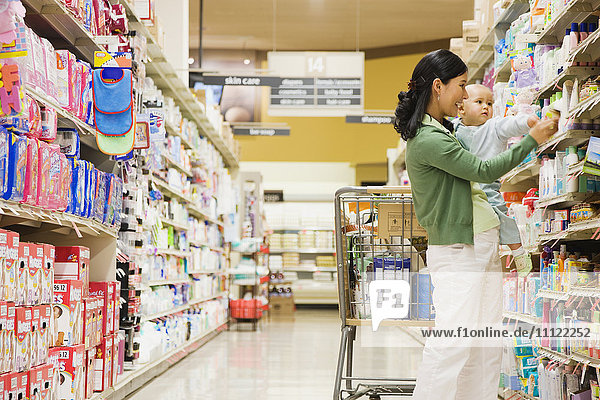 Mother shopping in grocery store with baby