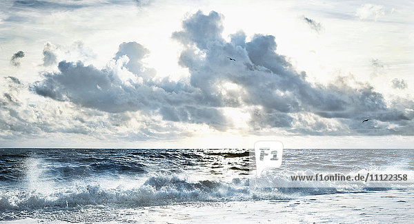 Cloudy sky over stormy waves on beach