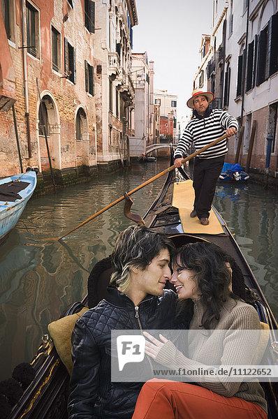 Romantic Italian couple riding in gondola through canal