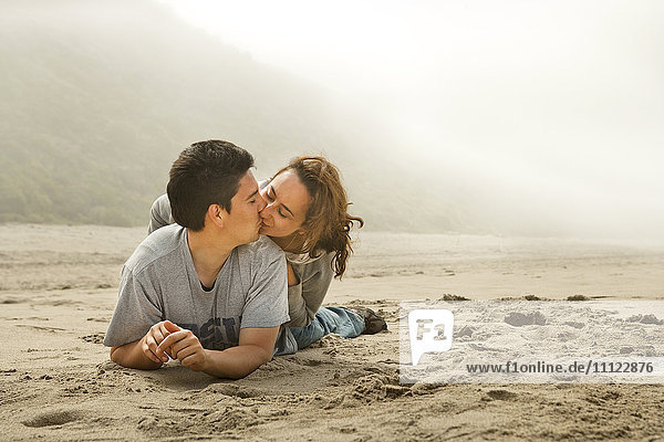 Hispanic couple kissing on beach Hispanic couple kissing on beach