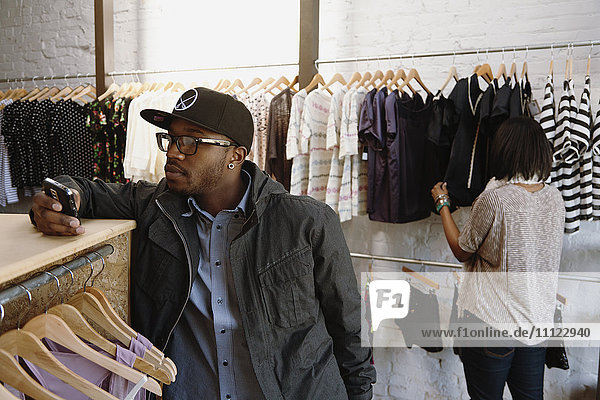 African American man text messaging on cell phone in clothing store