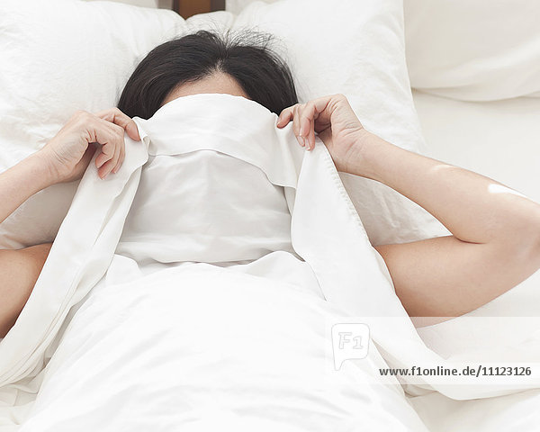 Hispanic woman in bed covering her face