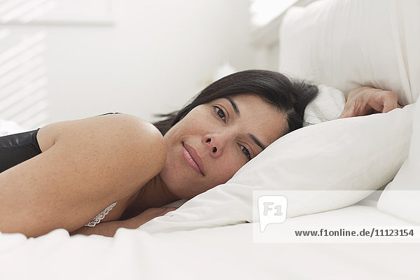 Tranquil Hispanic woman laying in bed