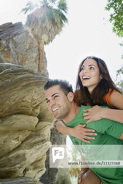 Hispanic man giving girlfriend piggyback ride