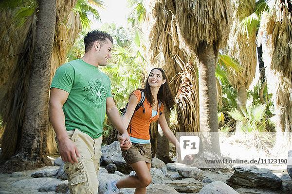 Hispanic couple hiking in tropical area