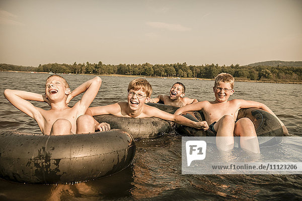 Caucasian boys with inner tubes in water