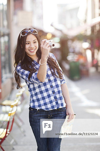 Chinese woman taking pictures with digital camera