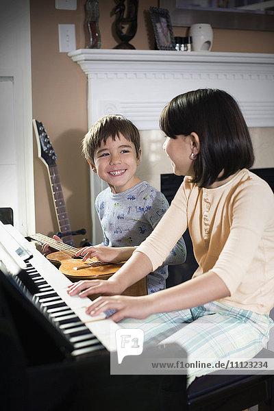 Hispanic children playing music in living room
