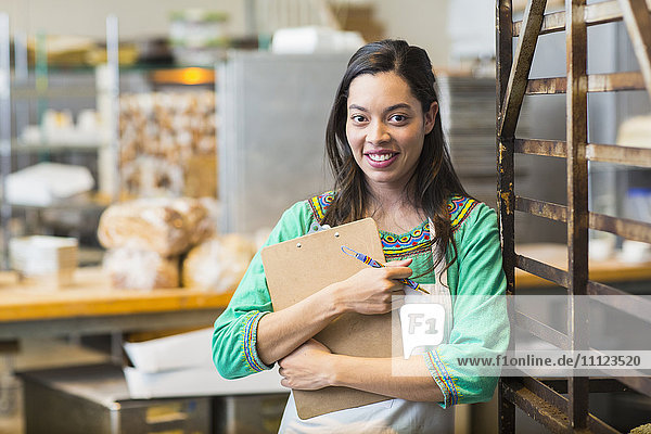 Mixed race woman working in bakery kitchen