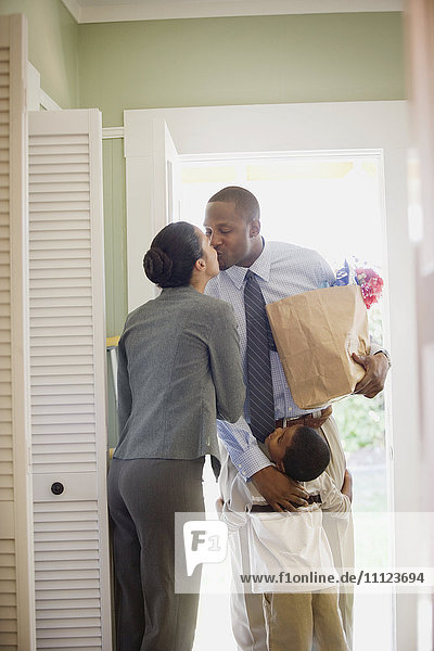 African father with groceries greeting family