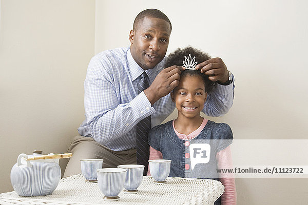 African father and daughter posing with tiara