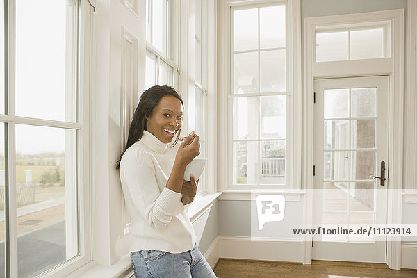 African woman eating in empty room