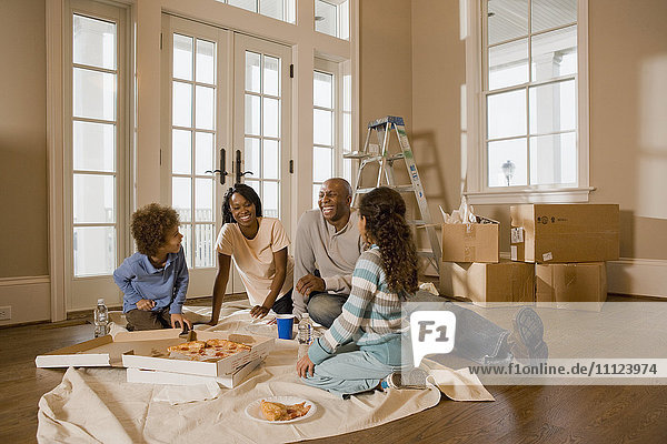 Family eating on floor in new home