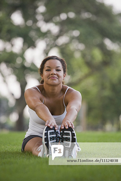 Mixed race woman sitting on grass stretching