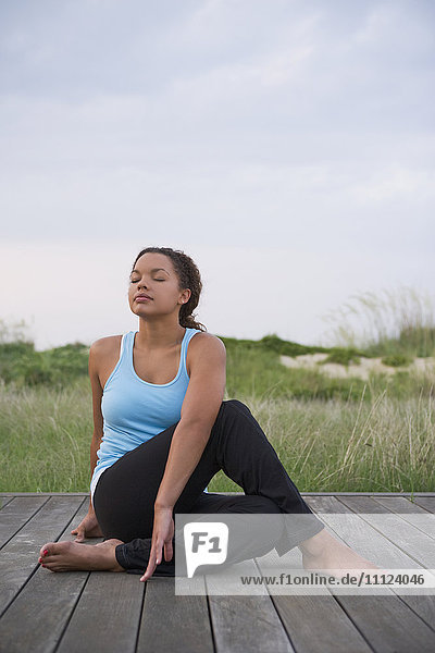Barefoot mixed race woman stretching on deck