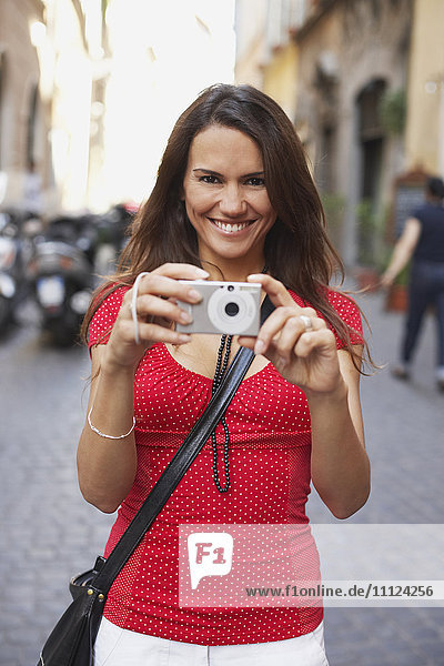 Tourist woman holding digital camera