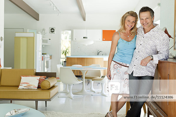 Couple standing together in living room