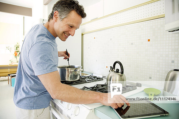 Man cooking in kitchen and looking at digital tablet