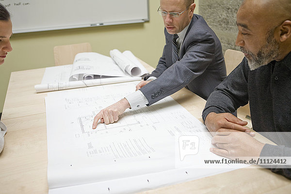 Businesspeople reviewing blueprints in meeting
