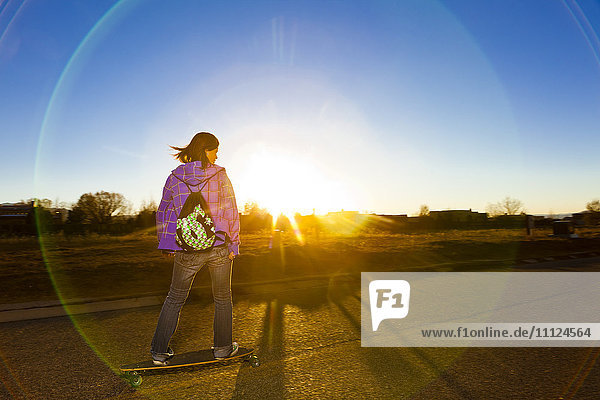 Chinese girl skateboarding on road at sunset