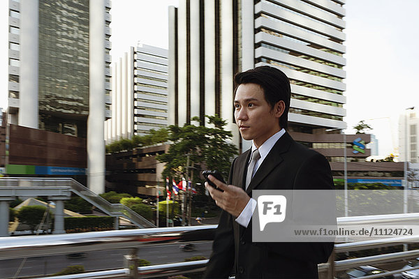 Asian businessman text messaging on cell phone outdoors