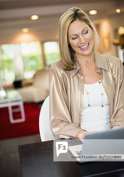 Caucasian woman using laptop at desk