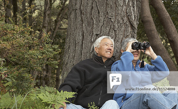 Senior Asian couple with binoculars outdoors