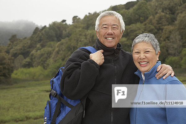 Senior Asian couple with backpack outdoors