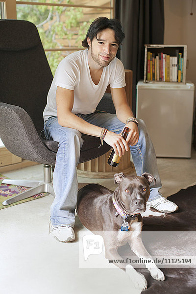 Mixed race man drinking beer and sitting with dog