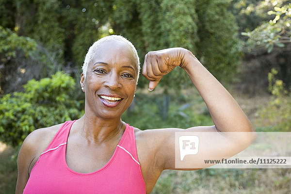 Mixed race woman flexing muscles outdoors