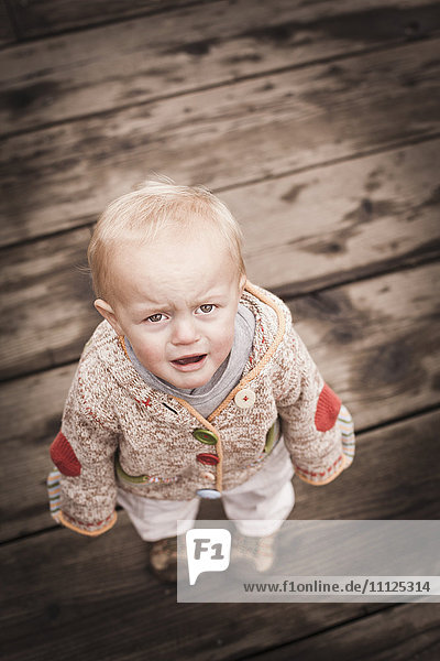 Frowning Caucasian boy standing outdoors